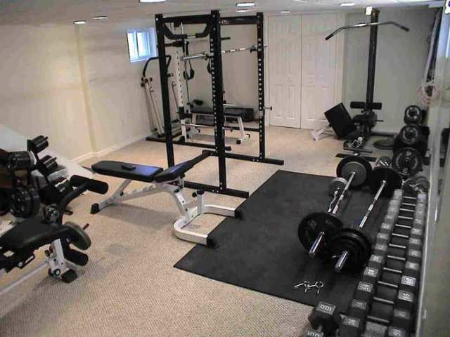 barbells in a home gym with squat rack